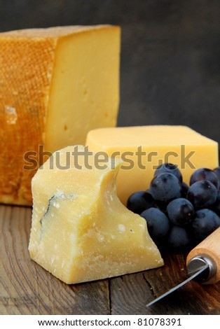 Cheese platter with grapes on a wooden black background - stock photo