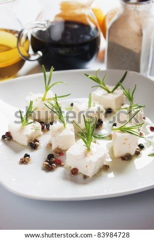 Cheese salad with rosemary and peppercorn on white plate