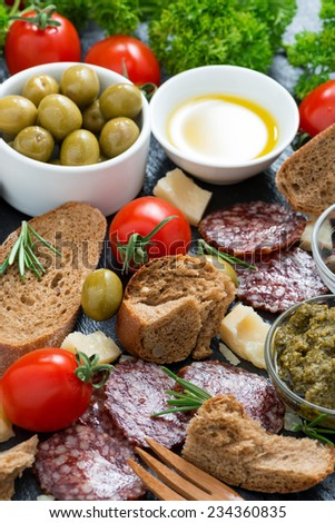 cheese, salami and various Italian appetizer, vertical, top view - stock photo