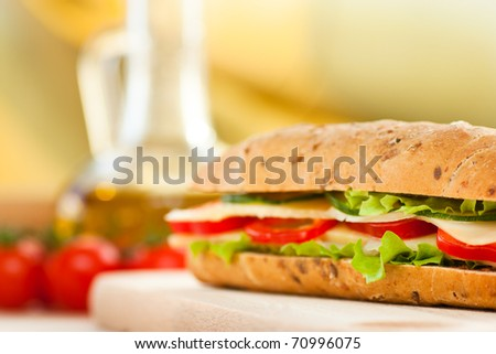 Cheese sandwich with paprika and green lettuce. Focus is on the right upper bread half. Shallow depth of field.