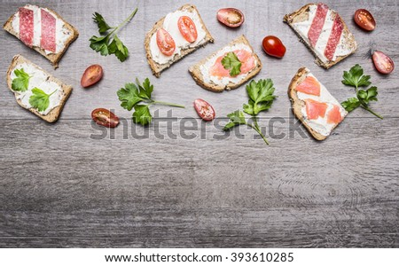 cheese sandwiches with tomatoes on a branch and herbs  cherry tomatoes and salmon on wooden rustic background top view border ,place for text  with parsley - stock photo