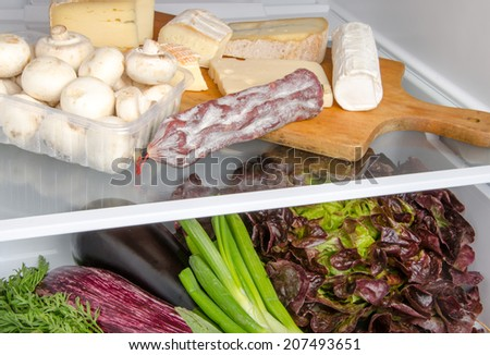 Cheese, sausage, mushrooms and different vegetables inside a refrigerator - stock photo