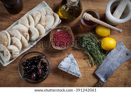 Cheese serving with various ingredients in a rustic style kitchen decor   - stock photo