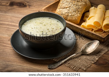 Cheese soup in a black plate on the rustic wooden background. - stock photo