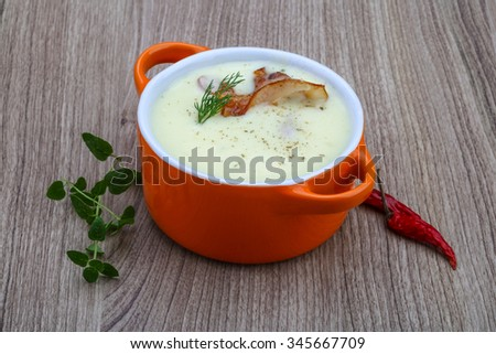 Cheese soup with bacon and herbs on the wood background