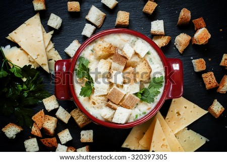 Cheese soup with croutons in red portioned saucepan, top view - stock photo