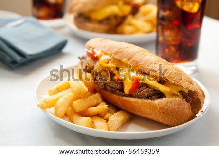 cheese steak sandwich accompanied by fries and an ice cold cola