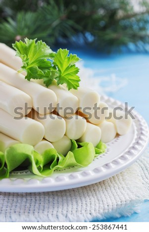cheese sticks and lettuce on a plate on the table. cheese and dairy products. selective focus - stock photo