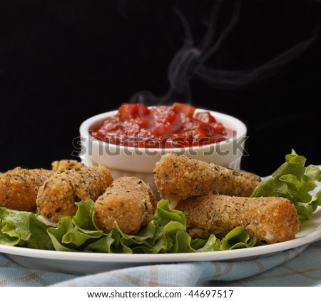 cheese sticks appetizer on salad with very hot salsa sauce. Smoke on the salsa with a black background. - stock photo