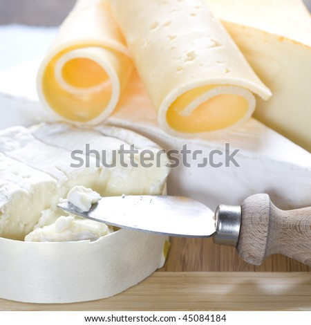 Cheese still life on a wooden board - stock photo