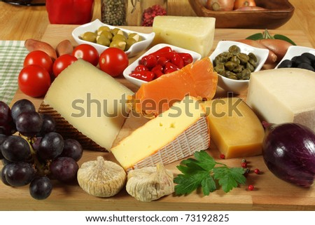 Cheese table. Cuisine delicacies with olives, peppers, grapes and capers.