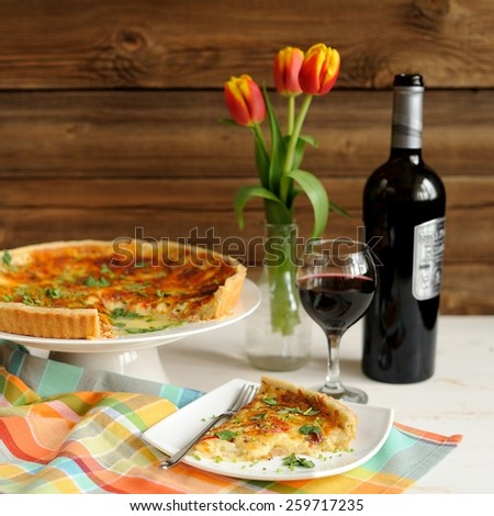 Cheese tart with red wine and red tulips on wooden background - stock photo