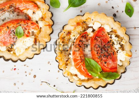 Cheese tart with tomato and basil leaves - stock photo