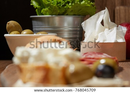 Cheese, vegetables, fruits and spices. Bread, olives and crackers. Mediterranean diet and cuisine. Dark background.