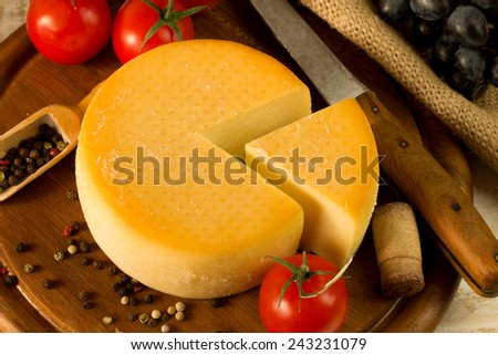 Cheese wheel on a wooden cutting board - stock photo