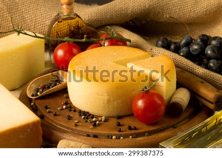 Cheese wheel on wooden cutting board - stock photo
