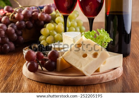 Cheese with a bottle and glasses of red wine on wooden table - stock photo