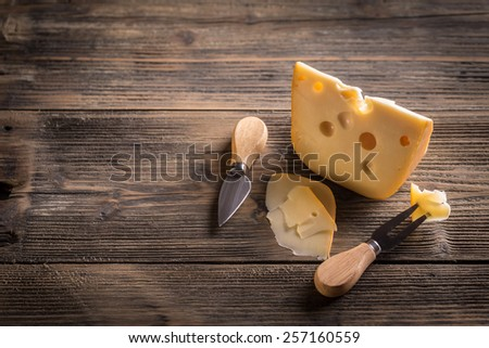 Cheese with a cheese knife and fork - stock photo