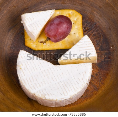 Cheese with a white mold, grapes and a cracker - stock photo