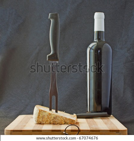 Cheese with big fork and bottle of red wine - stock photo