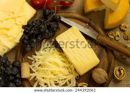 cheese with grape and nuts on a cutting board - stock photo