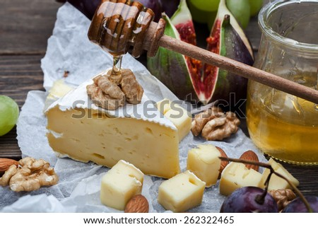 Cheese with grapes, honey and nuts on dark wooden background - stock photo