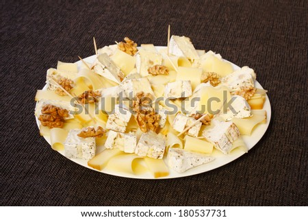 Cheese with nuts serve on plate with brown background - stock photo