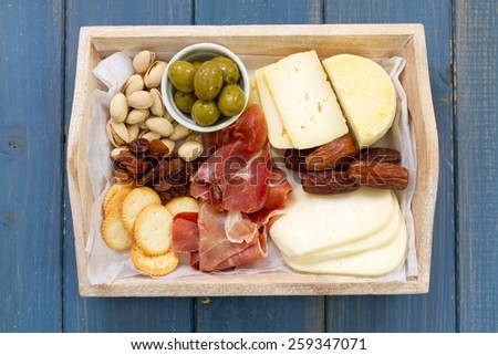 cheese with prosciutto, bread, dry fruits and nuts - stock photo