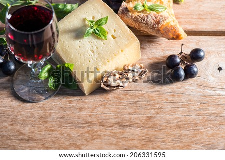 cheese with red wine, walnuts, basil leaves and grapes. food ingredients. low key style picture. selective focus