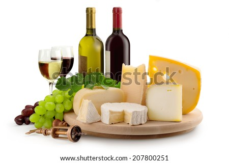 cheeseboard, grapes, wineglasses and wine bottles - stock photo