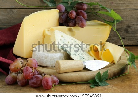 cheeseboard (Maasdam, Roquefort, Camembert) and grapes for dessert - stock photo