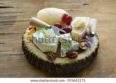 cheeseboard with assorted cheeses (parmesan, brie, blue, cheddar) - stock photo