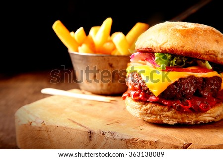 Cheeseburger and french fries on a countertop on old wooden background - stock photo