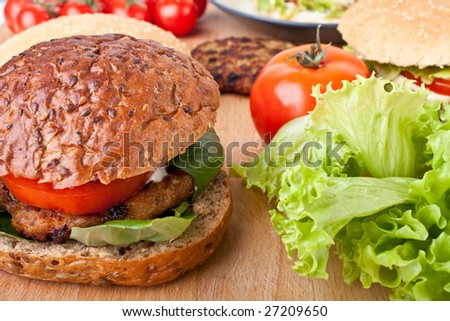 cheeseburger and ingredients for another burger - stock photo