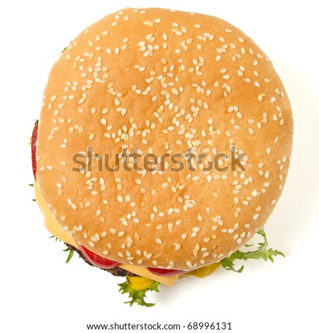 Cheeseburger and Mustard in sesame seeded bun isolated on white from overhead. - stock photo