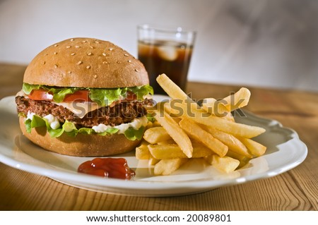 cheeseburger french fries and cola on a plate