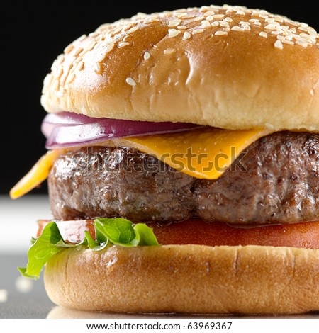 cheeseburger macro with black background and selective focus - stock photo