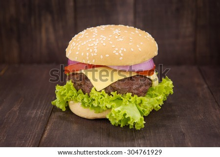 Cheeseburger on buns with succulent beef on the wooden background.