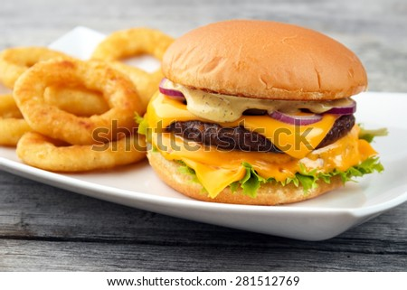Cheeseburger served with deep fry onion rings on the white square dish and wooden board background - stock photo
