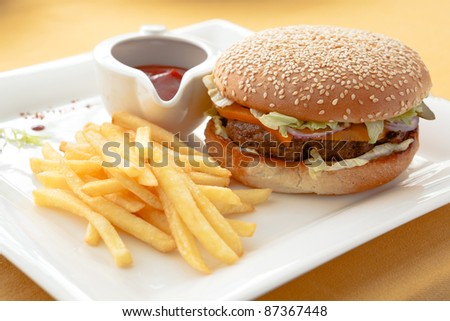 Cheeseburger with a mound of fries and ketchup. - stock photo