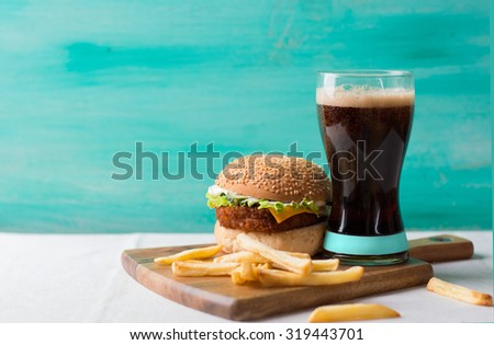 Cheeseburger with cola and potatoes, selective focus - stock photo