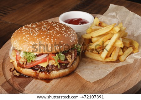 Cheeseburger with french fries and sauce on a brown wooden background