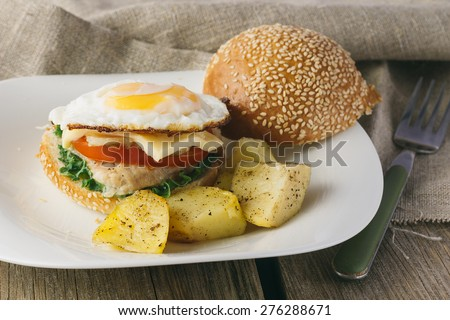 Cheeseburger with fried egg and potato wedges horizontal selective focus - stock photo