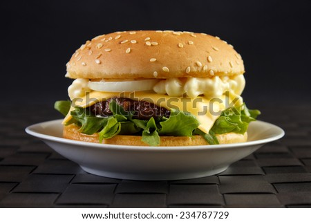 Cheeseburger with mayonnaise on dish with black background - stock photo