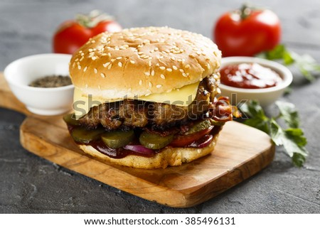 Cheeseburger with pickled cucumbers and bbq sauce - stock photo