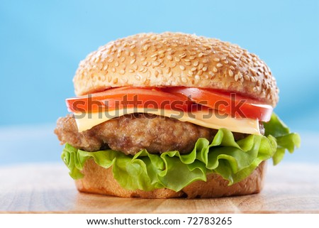 Cheeseburger with tomatoes and lettuce on a wooden table with blue background
