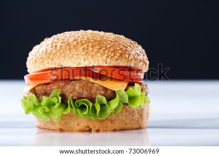 Cheeseburger with tomatoes and lettuce on black background