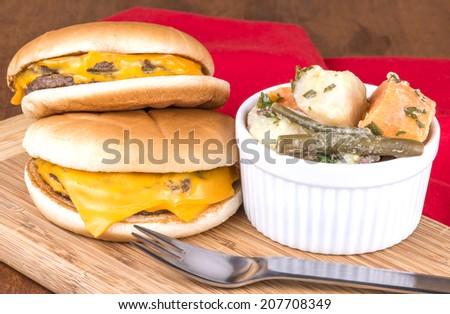 Cheeseburgers and potato salad - stock photo