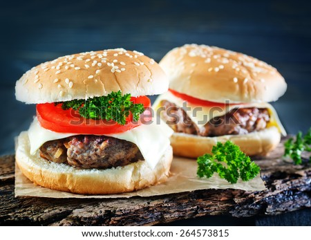 cheeseburgers on board and on a atble - stock photo