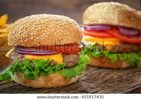 Cheeseburgers on wooden background with copy space